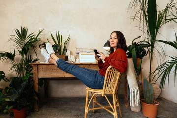 Woman using her phone in office full of plants.