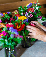 Hands working arranging colorful flowers in jars on a farmstead for a farm to table dinner