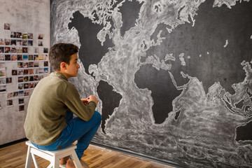 Boy drawing world's map in the classroom
