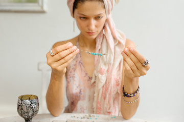 the girl is engaged in needlework from natural stones and beads