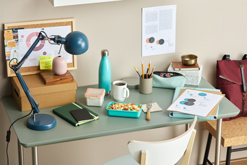 Modern table with lamp, box, documents and office lunch.