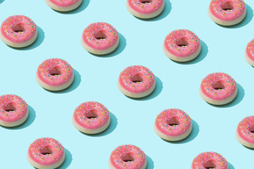 Trendy sunlight Summer pattern made with pink doughnut on bright light blue background. Minimal summer concept.