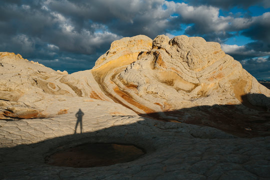 Shadow of photographer standing among vast sandstone rock formations at dusk, White Pocket