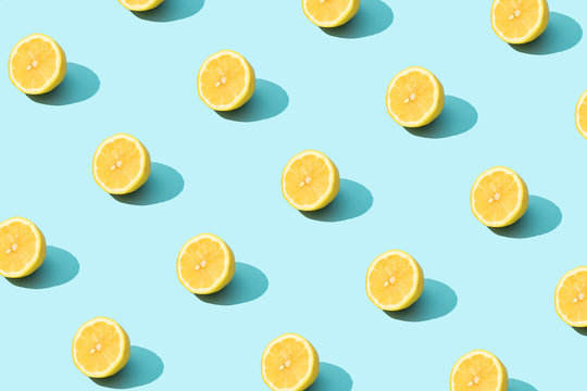 Trendy sunlight Summer pattern made with yellow lemon slice on bright light blue background. Minimal summer concept.