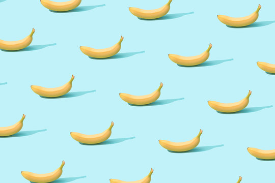 Trendy sunlight Summer pattern made with fresh banana fruit on bright light blue background. Minimal summer concept.
