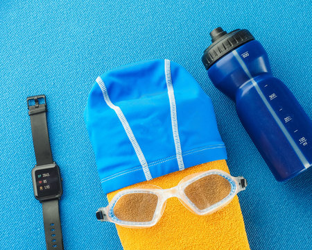 Flat lay composition with Goggles, swimming cap, fitness tracker and bottle of water, yellow towel equipment for swimming pool on blue background. top view. Swimming set.