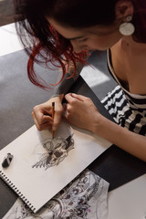 Girl drawing tattoo sketch in notebook