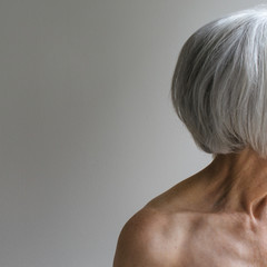 Senior topless woman on simple grey background