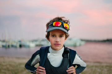 Teenage boy in sailing clothes at dusk