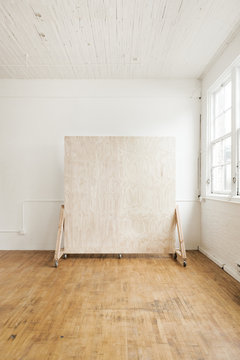plywood backdrop wall in white natural light studio with large windows