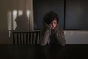 Quiet girl sitting at table in shadows