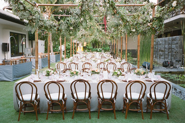 Outdoor, tropical wedding reception with hanging greenery garlands