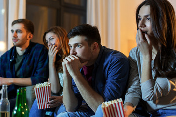 friendship and leisure concept - friends with beer and popcorn watching tv at home at night