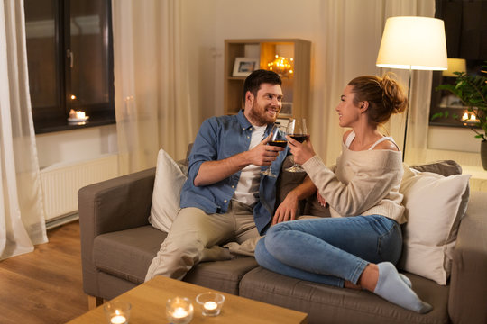 leisure, celebration and valentines day concept - happy couple drinking red wine at home in evening