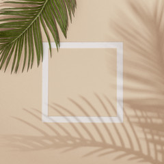 Wall Mural - Top view of green tropical leaves and shadows on sand color background. Flat lay. Minimal summer concept with palm tree leaf. Creative copyspace with paper frame.