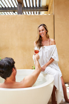 """Couple in outdoor bathtub at luxury resort """"""""toasting"""""""" with wine"""