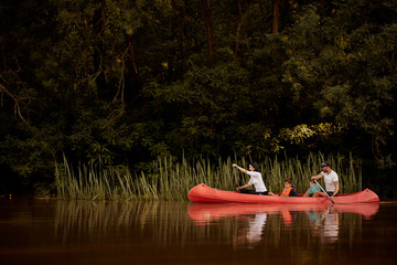 Family paddling red canoe in the river.