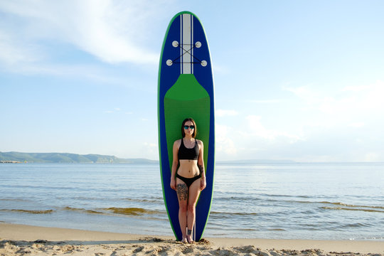 Young brunette woman standing with her paddle board on the beach