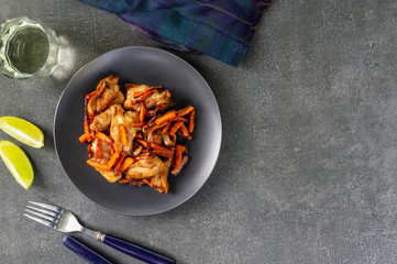 Teriyaki chicken with fried carrots and rice wine on a dark background