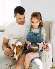 Dog near father and daughter with music box