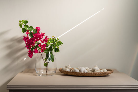 interior decor, glass vase with pink flowers and shells