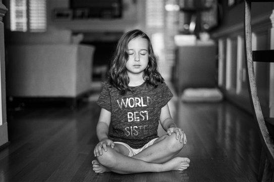 Beautiful young girl sitting on living room floor meditating