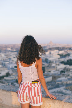 Unrecognizable woman looking at the city line of Victoria, Gozo