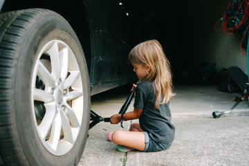 child changes tire on car