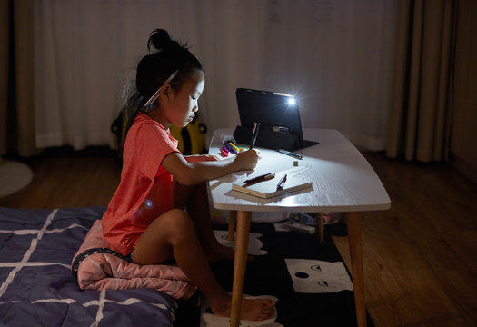 Beautiful asian little girl drawing and studying at home at night