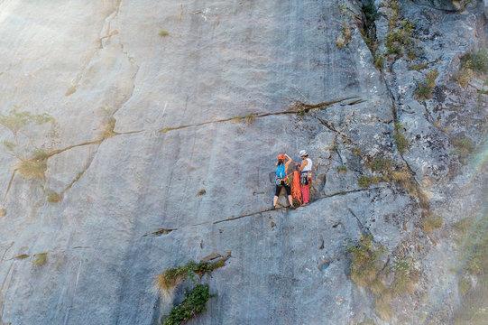 Senior man and young woman climbing a big rock wall.