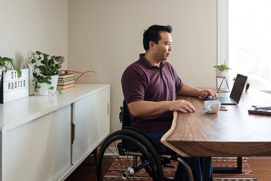 Asian man in wheelchair in home office.
