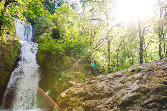 Woman hiking near waterfall in the the Pacific Northwest.