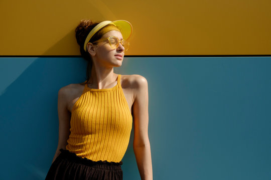 Young woman in trendy sportswear standing on a yellow-blue background