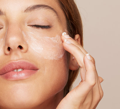 Woman portrait applying cream or moisturiser isolated In studio - skin care hydration closeup