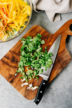 Cutting board with chopped parsley and onions