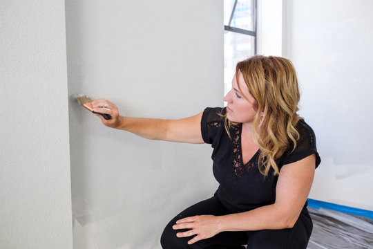 Woman Painting Wall Working as a Volunteer