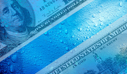 conceptual business and finance image of one hundred American dollar and raindrops
