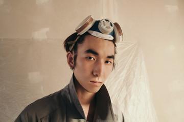 Asian guy in respirator looking at camera