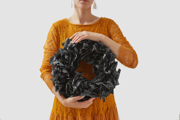 Handmade black holiday wreath from black paper in a girl hands on a background of an orange costume for Halloween.