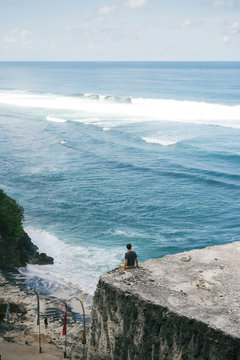 Relaxing man on high cliff of ocean
