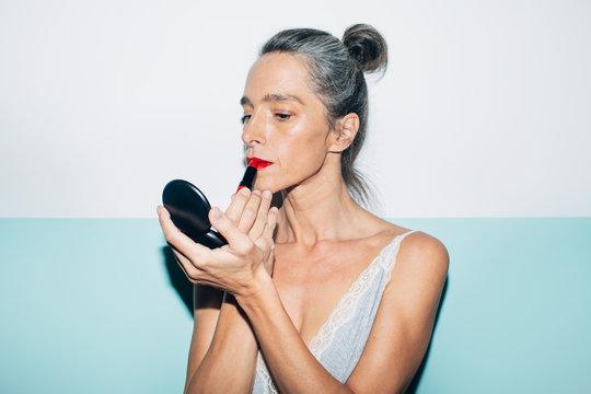 Senior woman with gray hair applying makeup