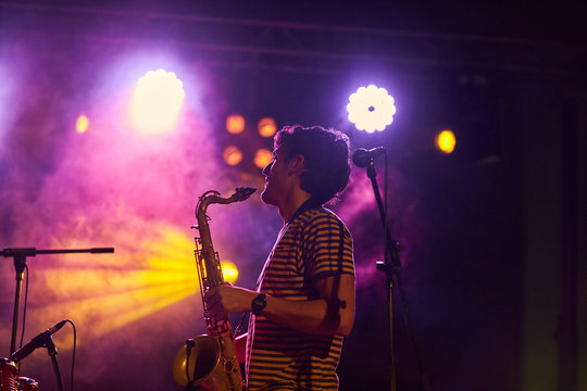 Young musician playing saxophone in a live concert