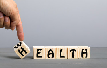 Hand flip wooden cube with word wealth to health