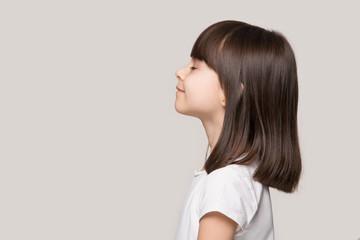 Profile of serene little girl isolated on grey studio background