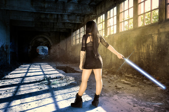 Warrior woman with a lightsaber waiting for her opponent