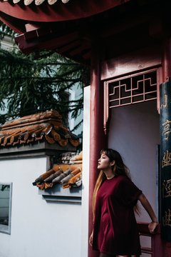 Stylish young woman posing by asian style architecture