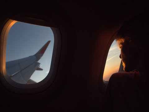 A girl looks in the airplane window during the flight