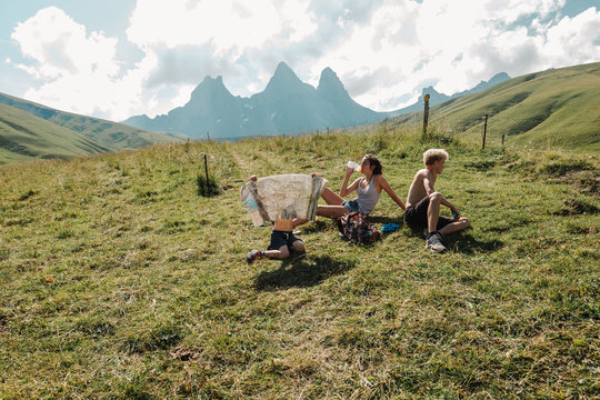 two teens and a child having rest at the top of mountain in the French alps