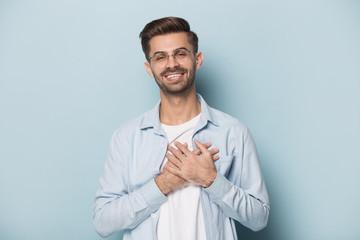 Grateful guy in glasses put hands on chest studio shot