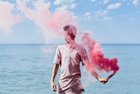 Man holding pink smoke bomb